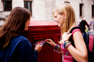 Two teenage girls putting postcards into a red letterboxの写真素材 [FYI02109371]