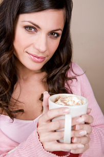 A young woman holding a cup of hot chocolateの写真素材 [FYI02109459]