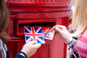 Two teenage girls putting postcards into a red letterboxの写真素材 [FYI02109511]