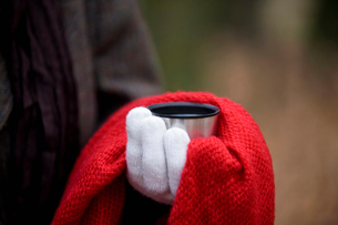 A woman holding a hot drink in autumn time, close upの写真素材 [FYI02109544]