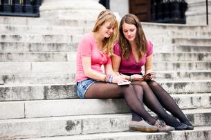 Two teenage girls sitting on steps, writing postcardsの写真素材 [FYI02109580]