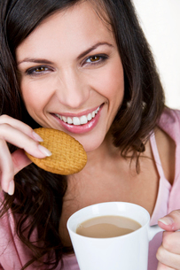A young woman holding a cup of tea, eating a biscuitの写真素材 [FYI02109671]