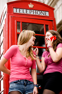 Two teenage girls laughing, one girl talking on her mobile pの写真素材 [FYI02109688]