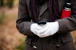 A woman holding a hot drink and flask outside in autumnの写真素材 [FYI02109740]