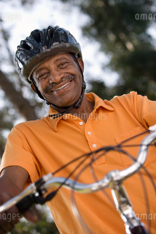 Active senior man wearing orange polo shirt and cycling helmet, sitting on bicycle in park, smiling,の写真素材 [FYI02109923]