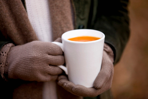 A woman holding a cup of soup in autumn time, close upの写真素材 [FYI02109930]