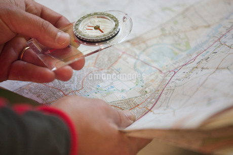 A man holding a map and compass, close upの写真素材 [FYI02109933]