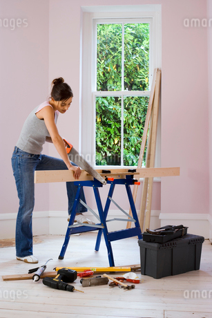 Woman doing DIY at home, cutting plank of wood on workbench with saw, side viewの写真素材 [FYI02109957]