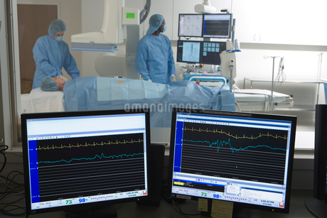 Doctors scanning patient in hospital, visual monitors in foregroundの写真素材 [FYI02109974]