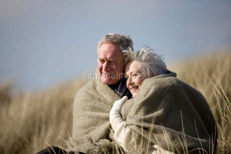 A senior couple sitting amongst the sand dunes, wrapped in aの写真素材 [FYI02109998]