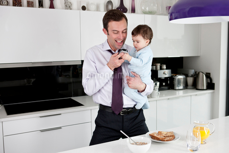 A father and his baby son looking at a telephoneの写真素材 [FYI02110047]