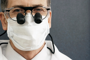 Male dentist wearing surgical mask and surgical loupes, close-up, front view, portraitの写真素材 [FYI02110086]