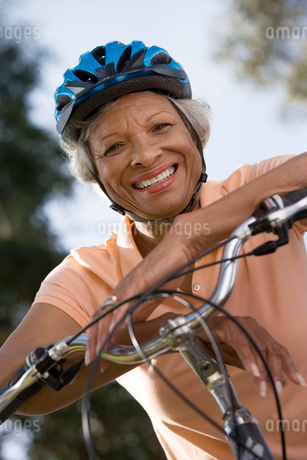Active senior woman wearing polo shirt and cycling helmet, sitting on bicycle in park, smiling, portの写真素材 [FYI02110091]