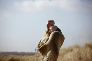 A senior couple standing in sand dunes, wrapped in a blanketの写真素材 [FYI02110146]
