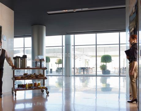 Waiter with trolley standing beside elevator door in lobby, businesswoman exiting second elevatorの写真素材 [FYI02110194]