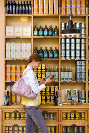 Female customer shopping for olive oil in grocery shop, holding bottle, reading label, profileの写真素材 [FYI02110218]