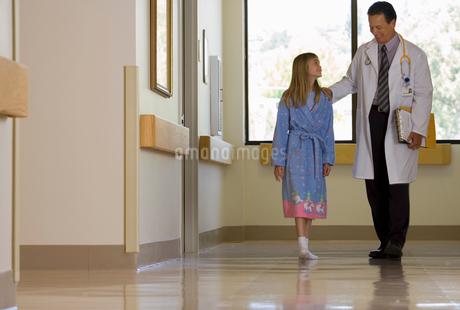 Doctor walking with patient in hospital corridor, girl (10-12) wearing dressing gown, smilingの写真素材 [FYI02110305]