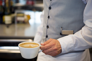 Waiter holding cup of coffee, close-up, mid-section, side viewの写真素材 [FYI02110346]