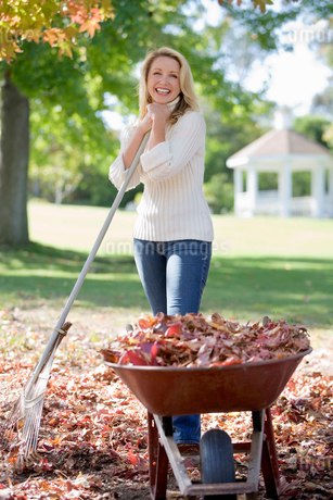 Woman collecting autumn leaves in garden, standing beside full wheelbarrow, leaning on rake, smilingの写真素材 [FYI02110349]