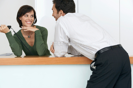 Businessman flirting with receptionist at reception desk, smiling, woman with telephone headsetの写真素材 [FYI02110361]