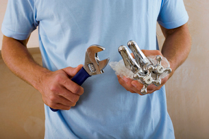 Man doing DIY at home, holding wrench and new faucets, close-up, mid-sectionの写真素材 [FYI02110377]