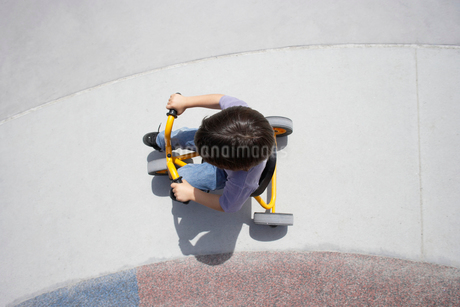 Boy (4-6) riding toy tricycle in playground, overhead viewの写真素材 [FYI02110406]