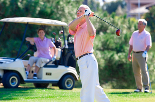 Three mature adults playing golf, mature man in pink polo shirt driving golf ball from tee, mature cの写真素材 [FYI02110417]