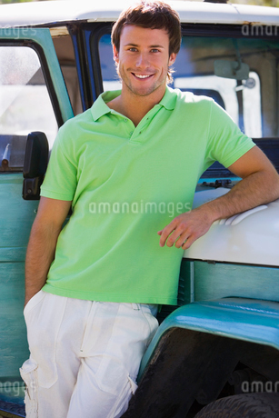 Young man, in green polo shirt, leaning against parked jeep, smiling, portraitの写真素材 [FYI02110526]