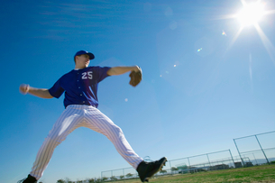 Baseball pitcher, in blue uniform, preparing to throw ball during competitive game, side view (lensの写真素材 [FYI02110554]