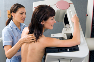 Patient having breast scan in hospital, nurse assisting, side viewの写真素材 [FYI02110619]