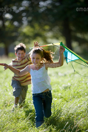 Brother and sister (7-10) playing with kite in field, boy chasing girl, smiling, front viewの写真素材 [FYI02110706]