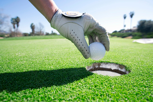 Person taking golf ball out of hole on putting green, close-up, side view, focus on hand and golf glの写真素材 [FYI02110769]