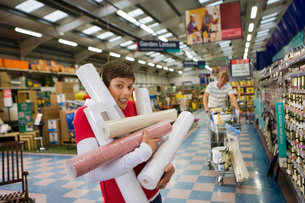 Woman struggling with rolls of wallpaper in DIY store, man pushing trolley in backgroundの写真素材 [FYI02110776]