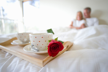 Mature couple sitting upright in bed, focus on breakfast tray with two coffee cups and single red roの写真素材 [FYI02110796]