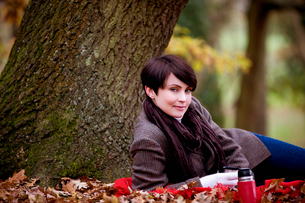 A woman sitting under a tree holding a hot drink in autumnの写真素材 [FYI02110876]