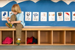 Blonde boy (4-6) sitting on bench in classroom, tying shoelace, alphabet cards on wallの写真素材 [FYI02110885]