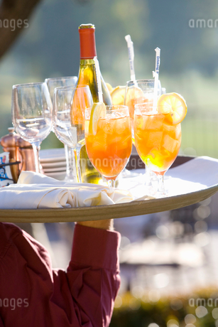 Waiter carrying cocktails and wine on tray, outdoors, close-up, rear view, mid-section, focus on forの写真素材 [FYI02110963]