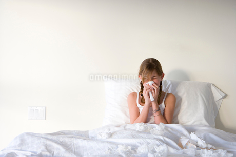 Girl (11-13) sitting upright in bed, blowing nose with handkerchief, front viewの写真素材 [FYI02110968]