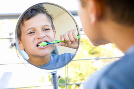 Boy (6-8) brushing teeth in bathroom, looking at reflection in mirrorの写真素材 [FYI02111022]