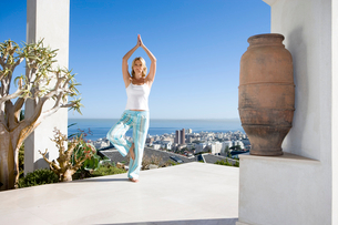 Young woman standing on balcony in tree pose yoga stance, portraitの写真素材 [FYI02111163]