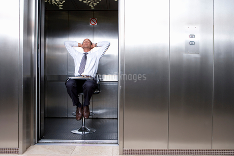 Mature businessman on stool in lift, laptop on lap, leaning back with head in handsの写真素材 [FYI02111164]