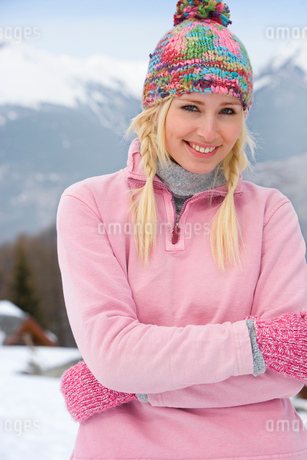 Young woman wearing woolen hat in snow, smiling, portrait, mountain range in backgroundの写真素材 [FYI02111179]