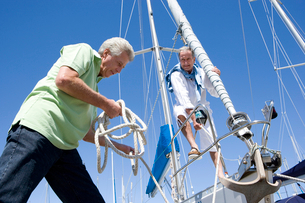 Two mature men preparing to set sail on yacht, one man untying mooring rope, smiling, low angle viewの写真素材 [FYI02111189]