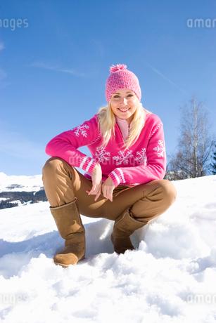 Young woman crouching in snow field, wearing woolen hat, smiling, portraitの写真素材 [FYI02111211]