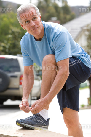 Active senior man, in blue t-shirt and shorts, tying trainer shoelace on driveway wall, side viewの写真素材 [FYI02111269]