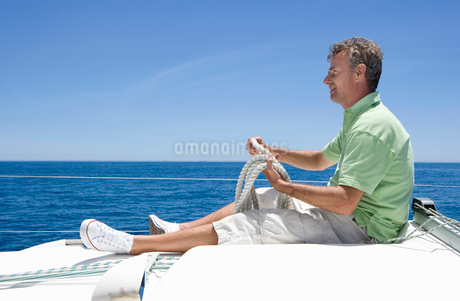 Man in shorts and green polo shirt sitting on deck of sailing boat out to sea, holding rope, smilingの写真素材 [FYI02111342]