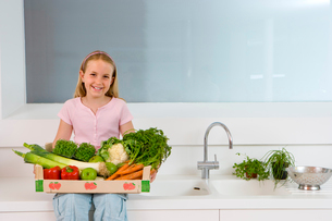 Girl (4-6) sitting on side in kitchen with box of vegetables on lap, smiling, portraitの写真素材 [FYI02111400]