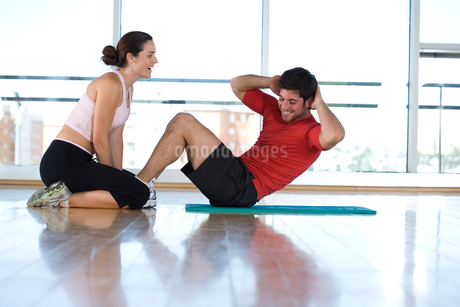 Woman helping man with sit-ups in gym studio, side viewの写真素材 [FYI02111439]