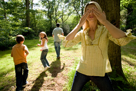 Family of four playing in forest, mother covering eyesの写真素材 [FYI02111460]