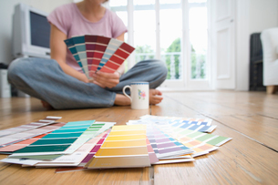 Young woman on floor with colour swatches, low sectionの写真素材 [FYI02111465]